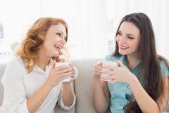 Amis féminins avec du café appréciant une conversation à la maison Photographie stock