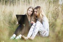 Amis féminins avec l'ordinateur portable extérieur Image libre de droits