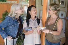 Amis féminins avec la brochure de la station de vacances Photos stock