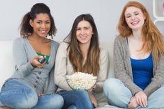 Amis féminins avec la cuvette à télécommande et de maïs éclaté sur le sofa Photo stock