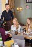 Amis féminins avec la nourriture sur le Tableau tandis que serveur Photos stock