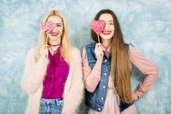 Amis féminins avec la sucrerie sur le fond bleu Photographie stock libre de droits