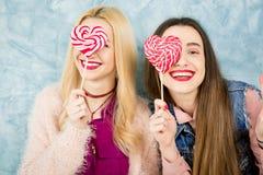Amis féminins avec la sucrerie sur le fond bleu Photos stock