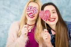 Amis féminins avec la sucrerie sur le fond bleu Photo stock