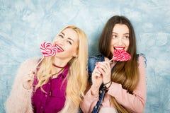 Amis féminins avec la sucrerie sur le fond bleu Photo libre de droits