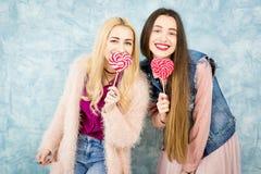 Amis féminins avec la sucrerie sur le fond bleu Photographie stock