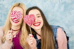 Amis féminins avec la sucrerie sur le fond bleu Image libre de droits