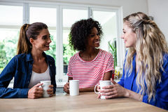 Amis féminins avec la tasse de café se reposant à la table Photos stock