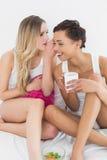 Amis féminins avec le bavardage de tasse de café dans le lit Photographie stock