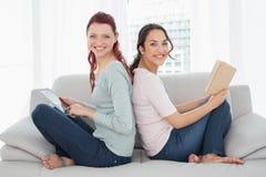Amis féminins avec le comprimé numérique et le livre à la maison Images libres de droits