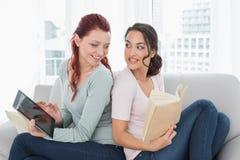 Amis féminins avec le comprimé numérique et le livre sur le sofa Image stock