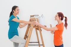 Amis féminins avec les pinceaux et l'échelle Photographie stock
