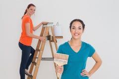 Amis féminins avec les pinceaux et l'échelle Photo stock