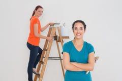 Amis féminins avec les pinceaux et l'échelle Images stock