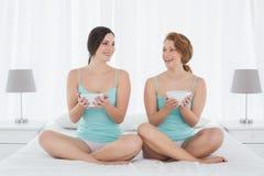 Amis féminins avec saladier se reposant sur le lit Images libres de droits