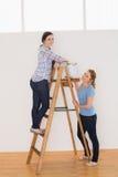 Amis féminins avec une échelle dans une nouvelle maison Images stock
