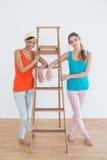 Amis féminins avec une échelle dans une nouvelle maison Image stock