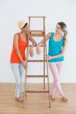 Amis féminins avec une échelle dans une nouvelle maison Photos stock