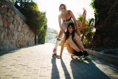 Amis féminins ayant l'amusement avec la planche à roulettes Image stock