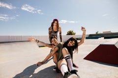 Amis féminins ayant l'amusement avec la planche à roulettes dans le parc de patin Images stock