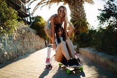 Amis féminins ayant l'amusement avec une planche à roulettes Photos libres de droits