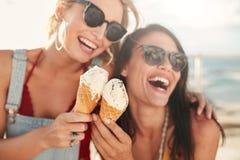Amis féminins ayant l'amusement et mangeant la crème glacée  Photos libres de droits