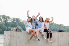 Amis féminins ayant l'amusement le week-end, sur le pique-nique dehors Jeunes de sourire s'asseyant à la frontière concrète et re photographie stock libre de droits