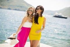 Amis féminins ayant l'amusement sur le bord de mer le jour ensoleillé Images libres de droits
