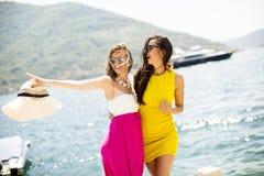 Amis féminins ayant l'amusement sur le bord de mer le jour ensoleillé Photo libre de droits