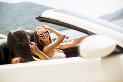 Amis féminins ayant l'amusement sur le bord de mer le jour ensoleillé Images stock