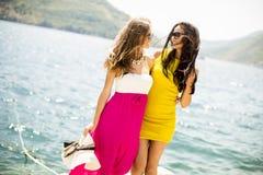 Amis féminins ayant l'amusement sur le bord de mer le jour ensoleillé Photos stock