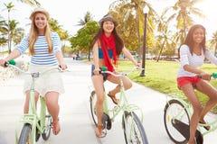 Amis féminins ayant l'amusement sur le tour de bicyclette Photos stock