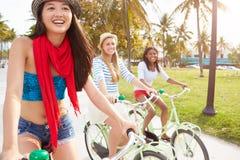 Amis féminins ayant l'amusement sur le tour de bicyclette Photo libre de droits