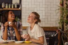 Amis féminins ayant l'amusement tout en ayant le café Photo stock