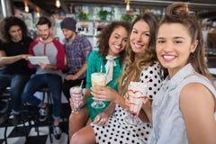 Amis féminins ayant la boisson tandis qu'amis masculins à l'aide du comprimé numérique dans le restaurant Photographie stock