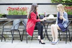Amis féminins ayant la conversation en café extérieur Photo stock
