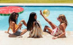 Amis féminins ayant la partie par la piscine Photos libres de droits