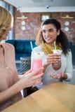 Amis féminins ayant le milkshake dans le cafétéria Photos stock