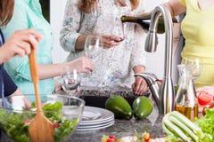 Amis féminins ayant une partie dans la cuisine Photographie stock libre de droits
