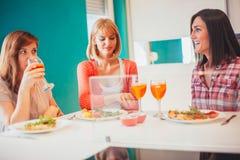 Amis féminins ayant une vie sociale à la maison Images stock