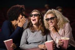 Amis féminins bavardant tout en observant le film Photographie stock libre de droits