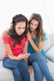Amis féminins bouleversés lisant le message textuel à la maison Photo stock
