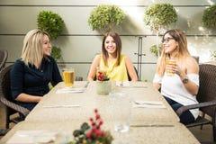 Amis féminins buvant dans une terrasse Photo libre de droits