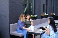 Amis féminins buvant du café et s'asseyant au café Photographie stock libre de droits