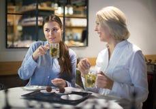 Amis féminins buvant du thé dans le café Photos libres de droits