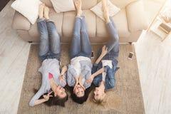 Amis féminins causant à la maison tout en se trouvant sur le plancher Photo libre de droits