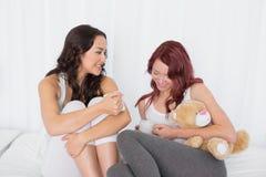 Amis féminins causant au-dessus du café dans le lit Image stock