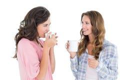Amis féminins causant tout en buvant du café Images stock