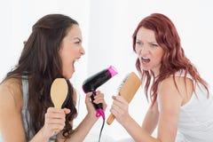 Amis féminins chantant dans la brosse à cheveux Photo stock