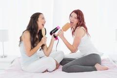 Amis féminins chantant dans la brosse à cheveux sur le lit Images stock